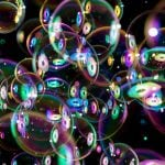 43746392 - colorful soap bubbles flying around on black background